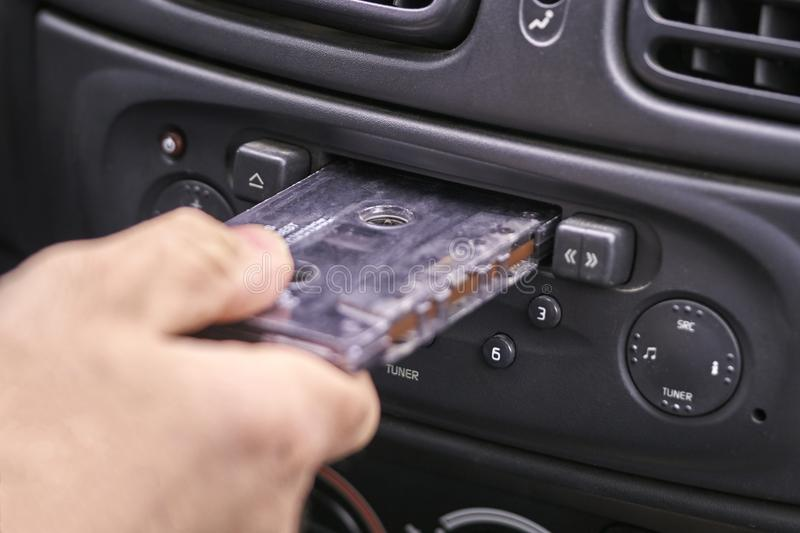 Hand inserting a music cassette into old car tape player royalty free stock photo