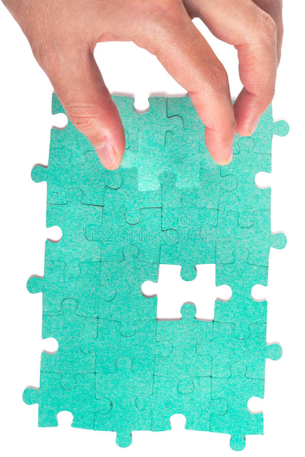 Hand inserting piece of green jigsaw puzzlel stock images