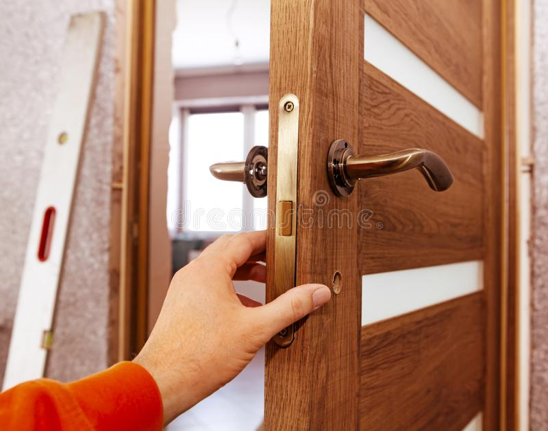 Hand of joiner. Who establishes a door in the room royalty free stock image