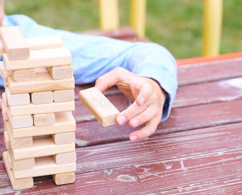 Hand of the kid playing wood blocks tower game for practicing physical and mental skill. Little caucasian boy is playing wood blocks tower game for practicing stock images