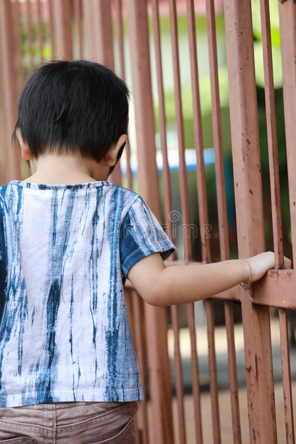 Hand of kid on the steel fence door royalty free stock photography
