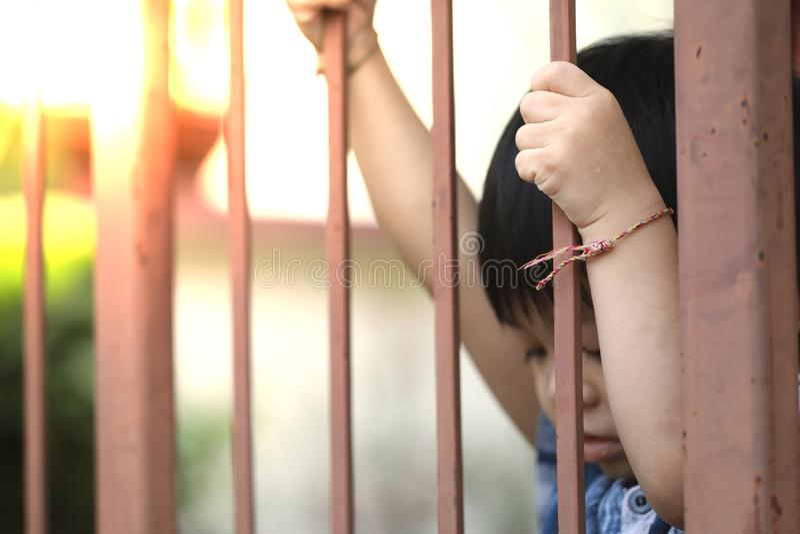 Hand of kid on the steel fence door stock image