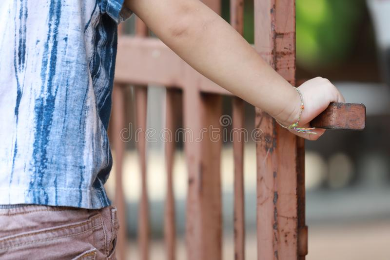 Hand of kid on the steel fence door royalty free stock images
