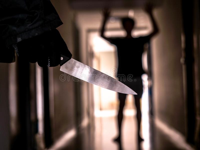 Hand with knife following young terrified in the apartment. man Bandit is holding a knife in hand, Threat Concept, Murder concept.  royalty free stock image