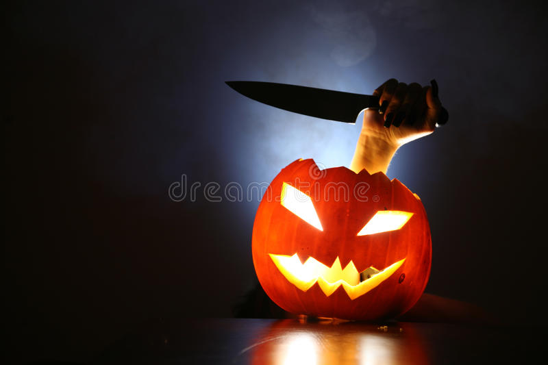 Hand with knife in Jack-o-lantern