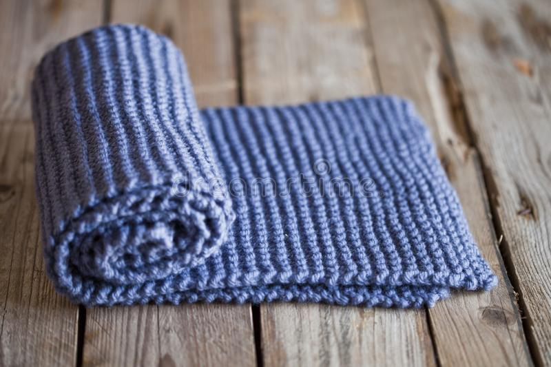 Hand knitted blue scarf. Hand knitted blue scarf on wooden background royalty free stock image