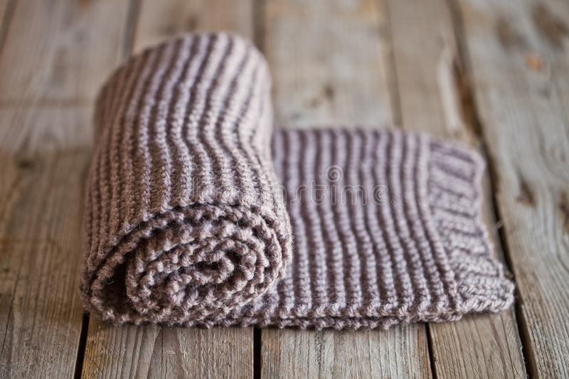Hand knitted brown scarf. On wooden background stock photos
