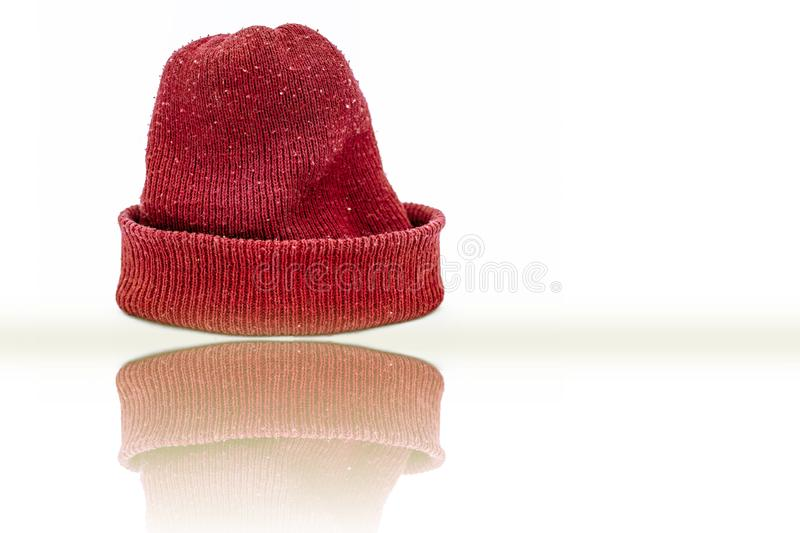 Hand knitted red-colored woolen cap isolated on white indicating Christmas. stock image