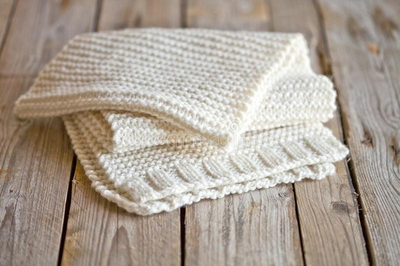 Hand knitted white scarf. Hand knitted white scarf on wooden background royalty free stock images