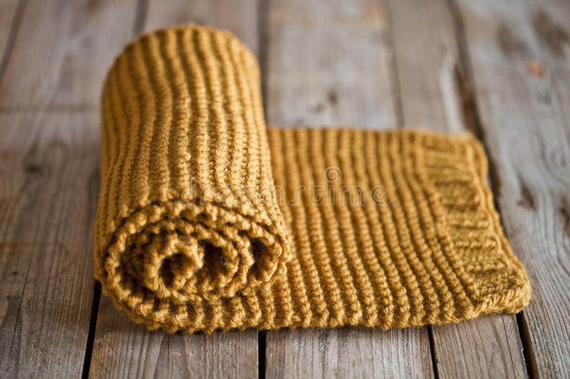 Hand knitted yellow scarf. Hand knitted yellow scarf on wooden background stock photography