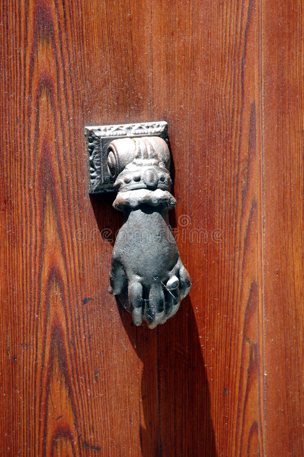 Hand knocker on dusty door. Oln door knocker shaped as a hand with ring on a dusty door royalty free stock images