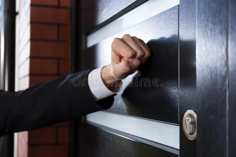 Hand knocking on the door. Close-up of hand knocking on the door stock photography