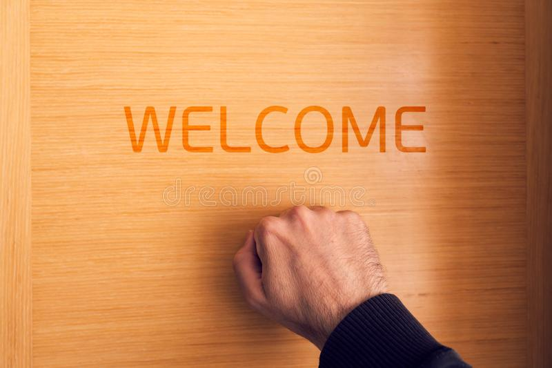 Hand knocking on door with welcome sign. Male hand is knocking on door with welcome sign for hospitality stock photo