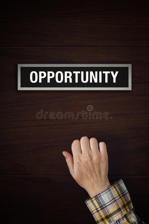 Hand is knocking on the doors of Opportunity. Female hand is knocking on Opportunity wooden door, conceptual image. Visitor or guest is at the door stock photo