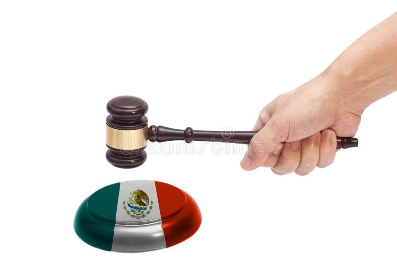 Hand knocking a Judge gavel at soundboard with Mexico flag. Isolated on white background royalty free stock photography