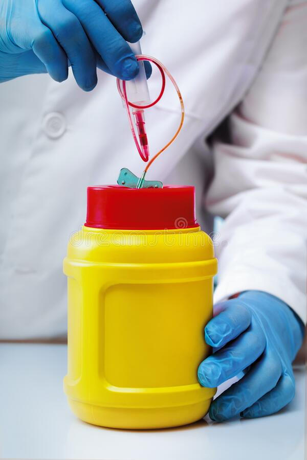 Hand of a laboratory technician removing material in a sharps container royalty free stock images