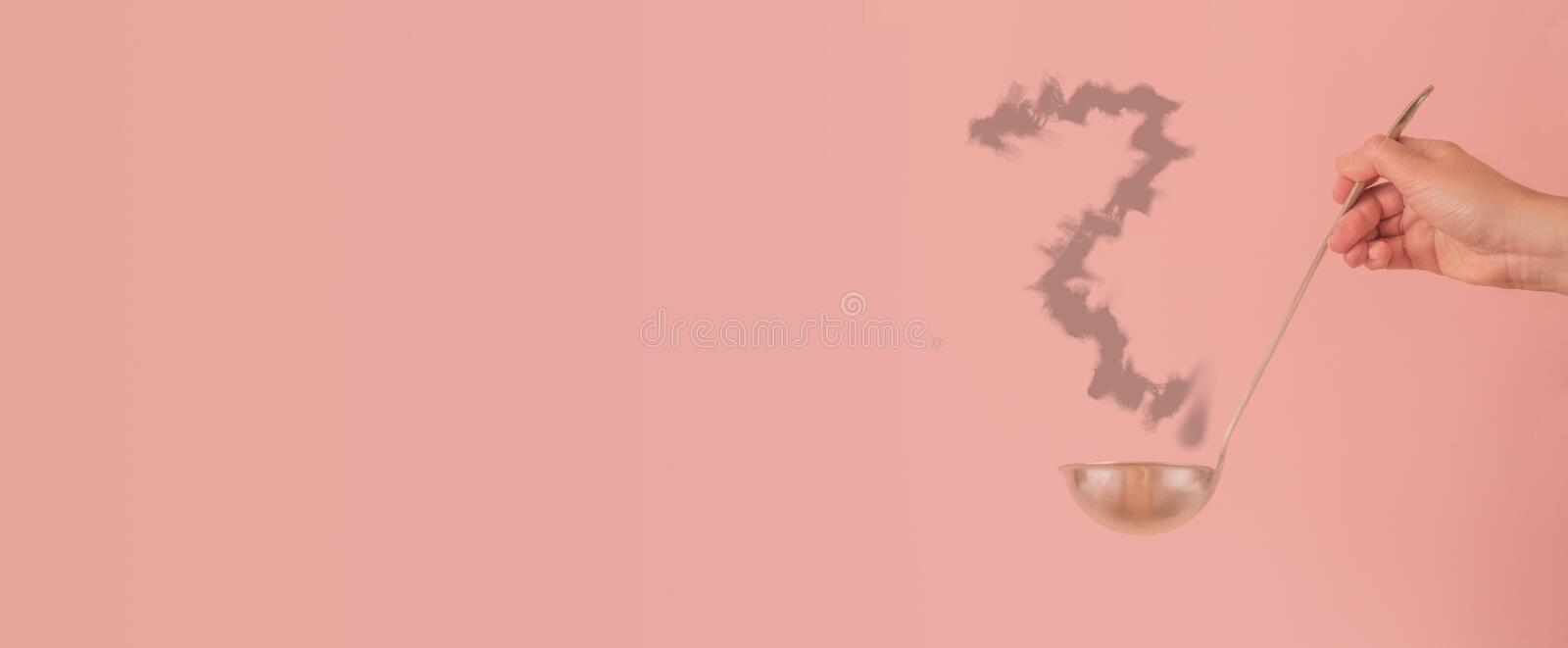 Hand with ladle with questioning on pink with copy space - What do I cook today concept royalty free stock images
