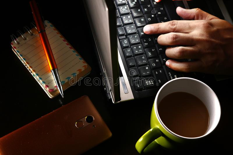 Hand on a laptop computer, cup of coffee, ballpen, notebook and a smartphone. Photo of a hand on a laptop computer, cup of coffee, ballpen, notebook and a stock photography