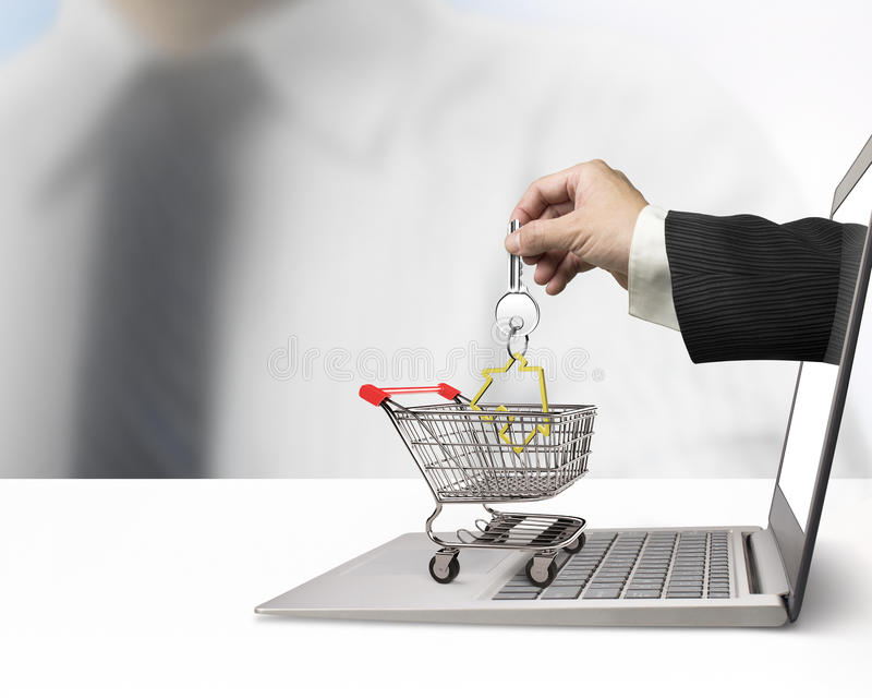 Hand from laptop screen taking house key in shopping cart. Male hand from laptop screen taking house key in the shopping cart, real estate online for sale or for stock photos