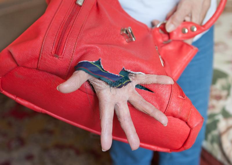 Hand in a leaky bag. Master carelessness royalty free stock image