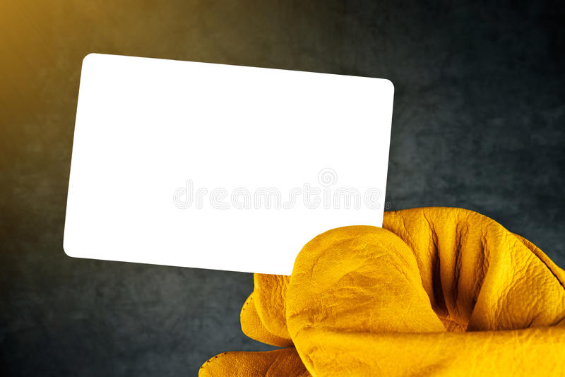Hand in Leather Construction Working Gloves Holding Blank Busine royalty free stock images