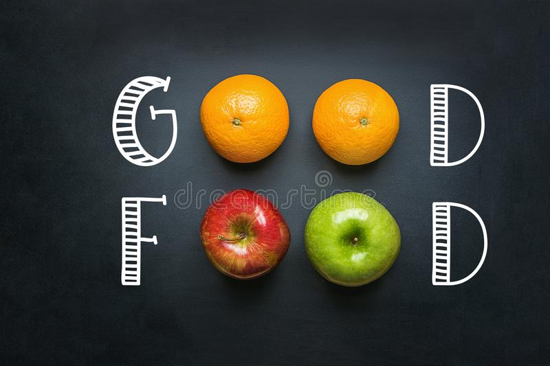 Hand Lettering Good Food on Black Chalkboard with Fruits Oranges Green Red Apples. Healthy Clean Eating Vegan Vitamins Energy. Concept. Creative Mixed Media royalty free stock photography