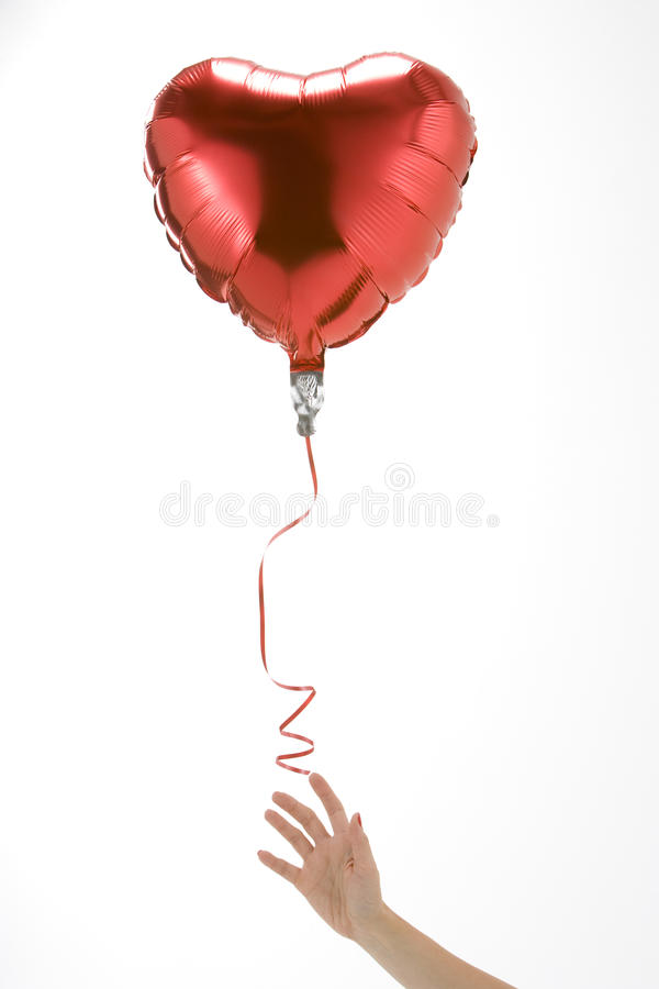 Hand Letting Go Of Heart Shaped Balloon stock photography
