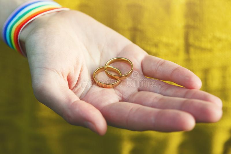 Hand with LGBT rainbow ribbon wristbands holding pair of golden wedding rings. Female hand with LGBT rainbow ribbon wristbands holding pair of golden wedding royalty free stock photography