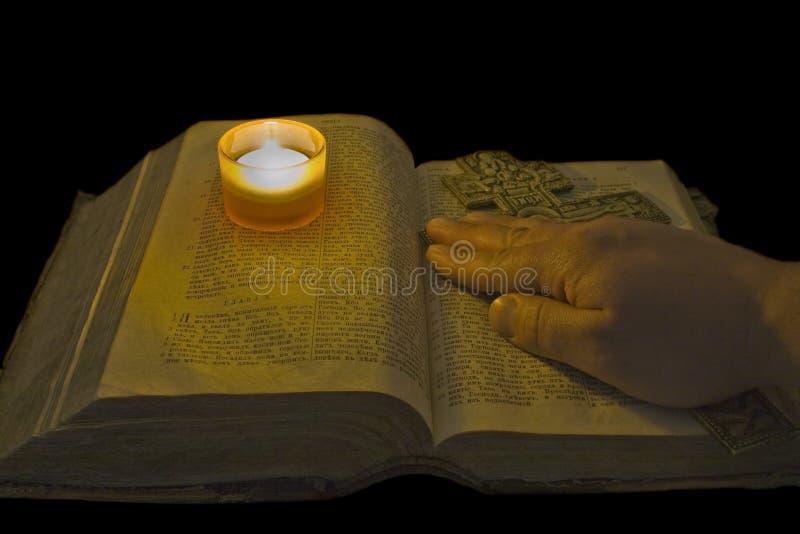 Hand liegt auf alter Bibel mit einem christlichen Kreuz lizenzfreie stockbilder