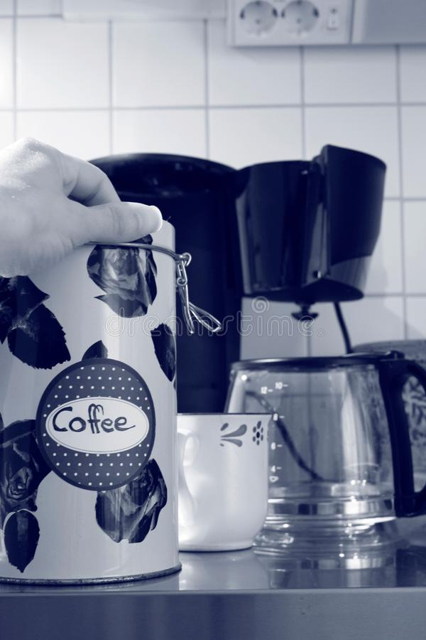 A hand lies on top of a coffee tin can, a cup and a coffee machine is seen in the background royalty free stock photo