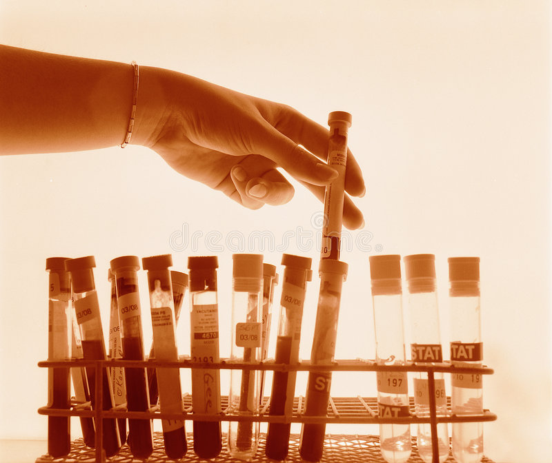 Hand lifting test tube. Woman's hand selecting test tube from rack against a backlit light source stock photo