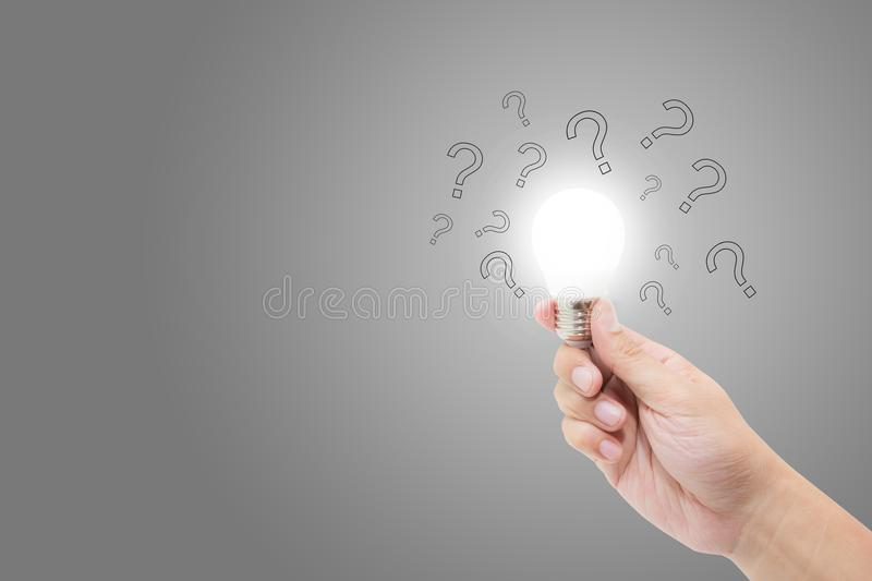 Hand with light bulb and question mark for solution, inspiration and brainstorm royalty free stock photos