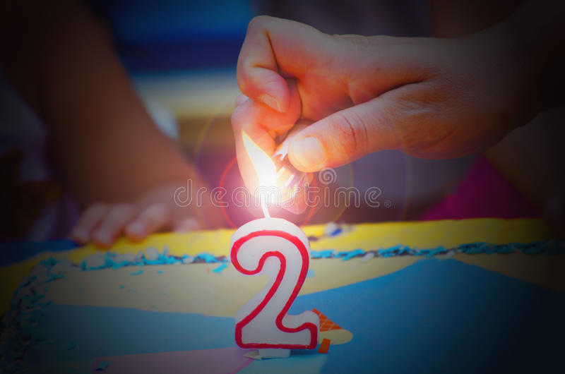 Hand with a lighter about to fire a two years birthday candle. jp royalty free stock photo