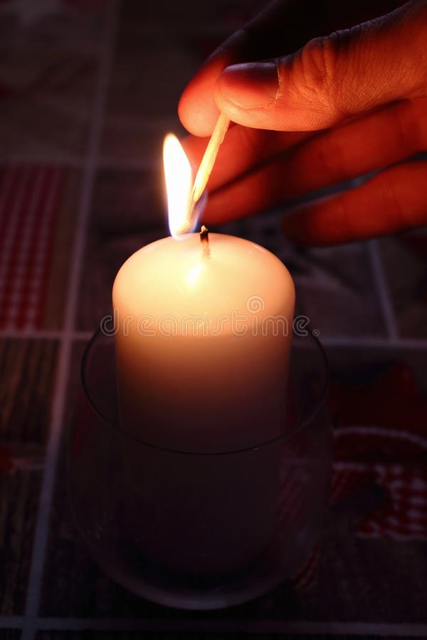 Hand lighting candle with burning flame. Christmas holiday decoration. Romantic love valentine`s day mood. stock photos