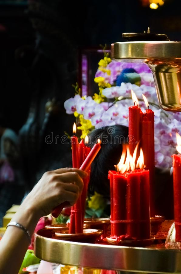 Hand lighting red candle by altar in Buddhist temple, Taiwan, China. Religious symbols, spirituality concept, faith, God. Buddha. Chinese folk religion royalty free stock photo