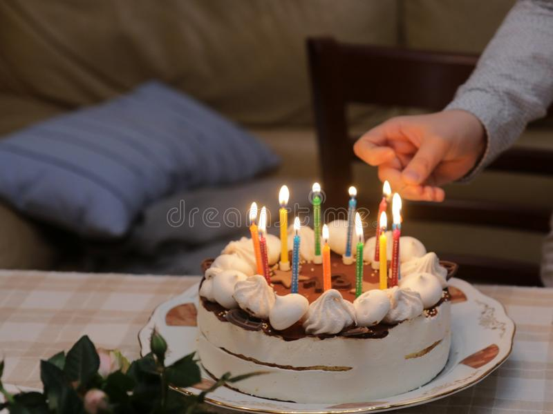 Hand lights the candles on birthday cake. royalty free stock photo