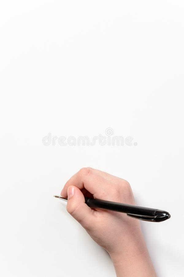 Hand of a little boy with a black pen on a white background stock photos