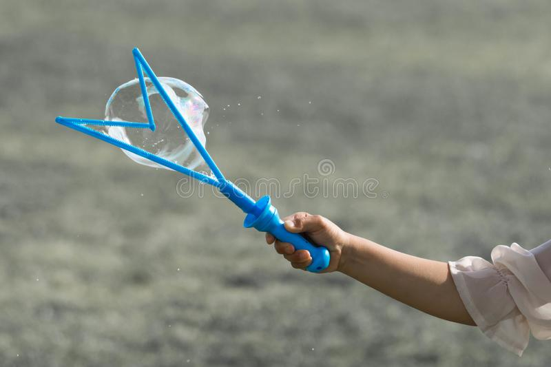 A hand of a little young girl holding a blue bubble maker and making bubbles. stock images