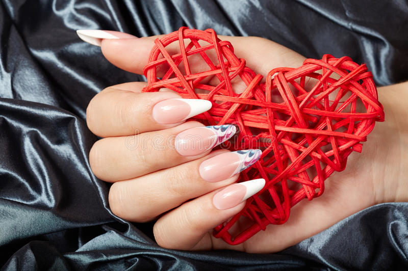 Hand with long artificial french manicured nails holding a heart. Hand with beautiful long artificial french manicured nails holding a heart royalty free stock images
