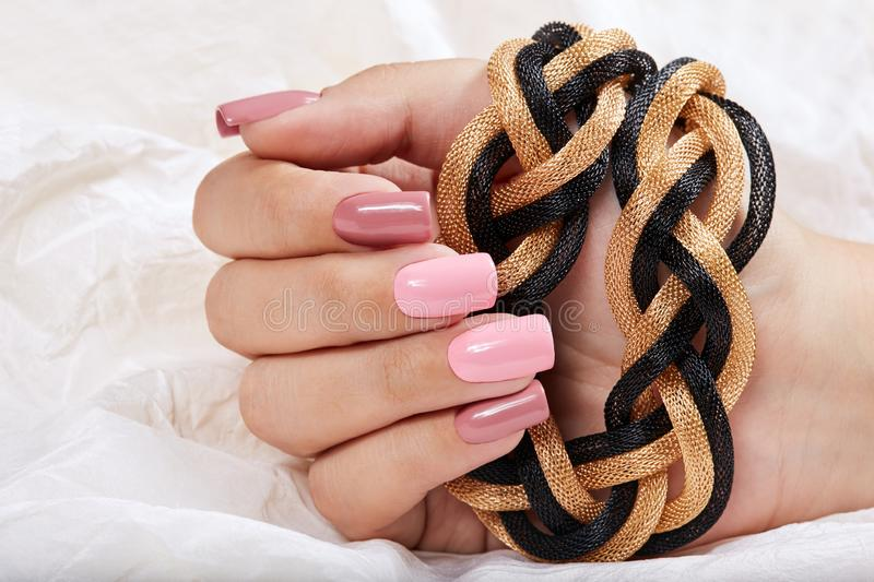 Hand with long artificial manicured nails colored with pink nail polish. Holding a necklace stock photography