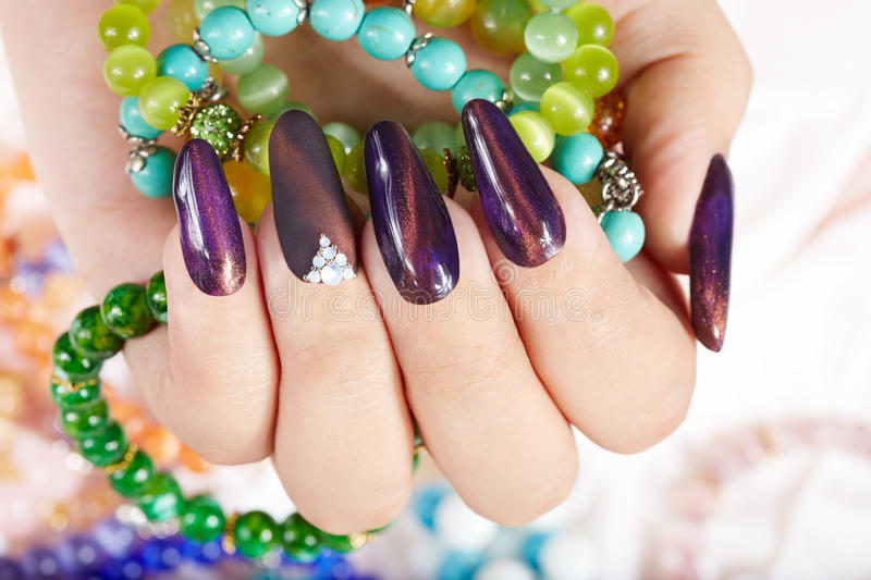 Hand with long artificial manicured nails holding bracelets. Hand with long purple artificial manicured nails holding colorful bracelets stock photos