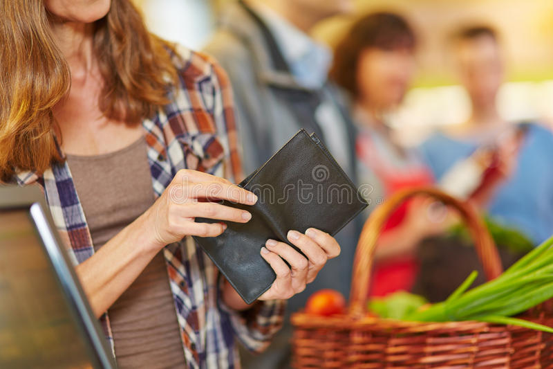 Hand looking for money in wallet stock photo