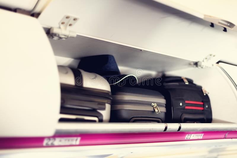 Hand-luggage compartment with suitcases in airplane. Carry-on luggage on top shelf of plane. Travel concept with copy royalty free stock photography