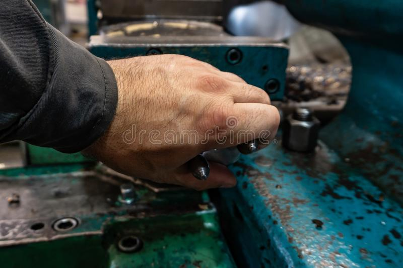 The hand of the machine operator creates a mechanical switch on the lathe.  royalty free stock photos