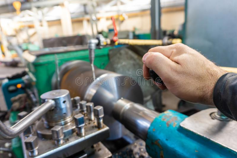 The hand of the machine operator creates a mechanical switch on the lathe.  stock photography