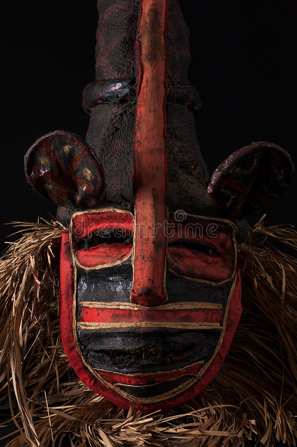 Hand made African mask with ropes simulating hair. Human face. I. Solated on black background.Isolated stock photos
