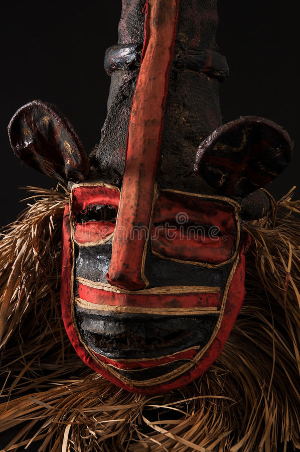 Hand made African mask with ropes simulating hair. Human face. I. Solated on black background. Isolated stock photography