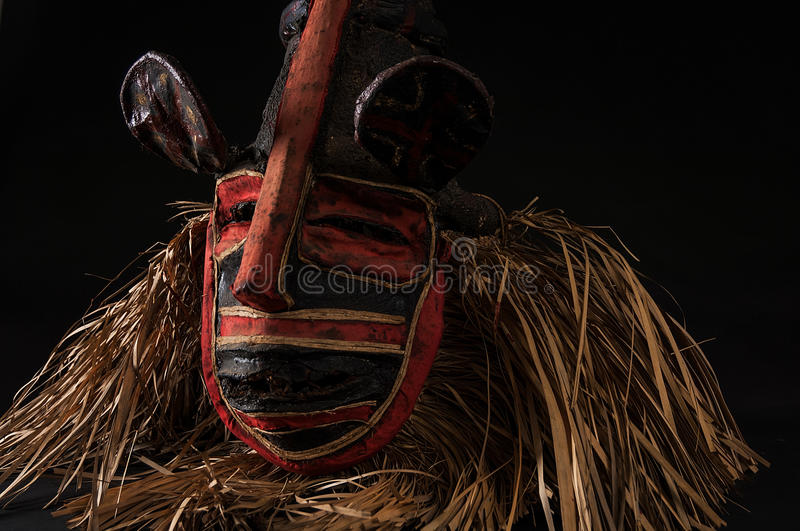 Hand made African mask with ropes simulating hair. Human face. I. Solated on black background. Isolated stock images