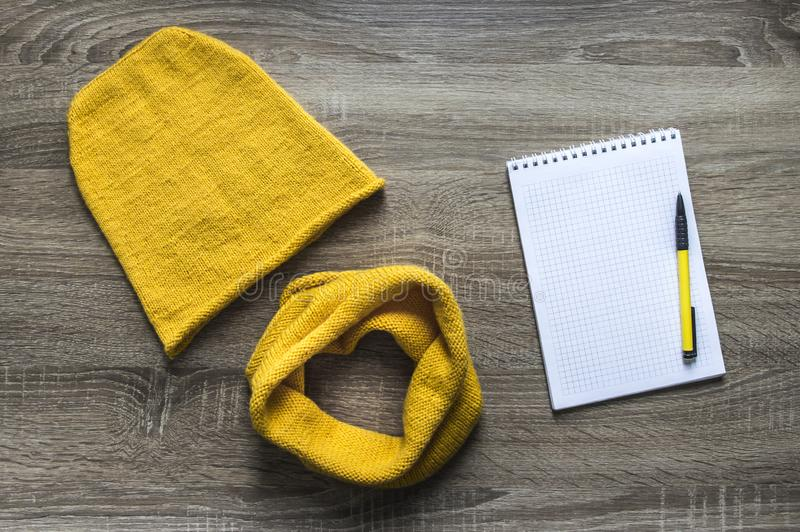 Background tree yellow snod scarf cap knitted with knitting needles facial smoothness mohair merino wool acrylic yarn notepad pen. Hand made background tree royalty free stock images