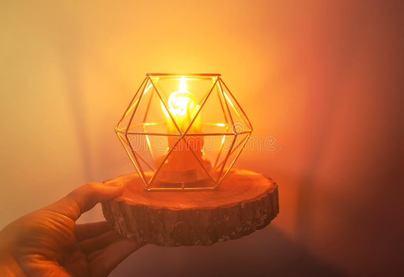 Hand made bee wax candle in a candleholder on wooden slice. Warm light of hand made natural bee wax dying candle in a candleholder on wooden slice royalty free stock image